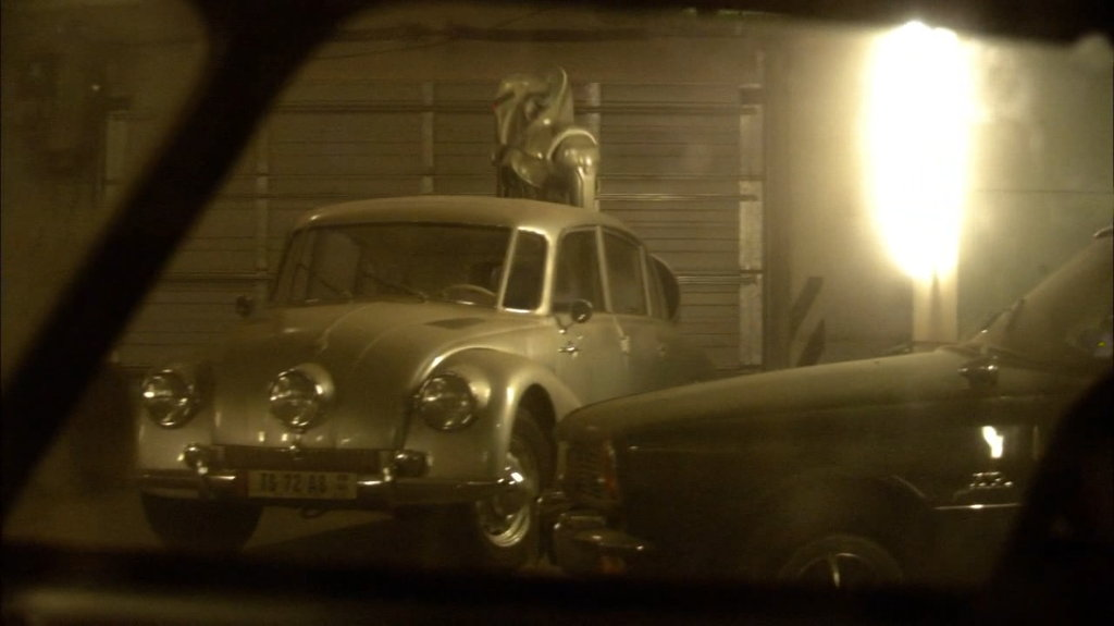 Cylon walking around some classic cars. Battlestar Galactica.