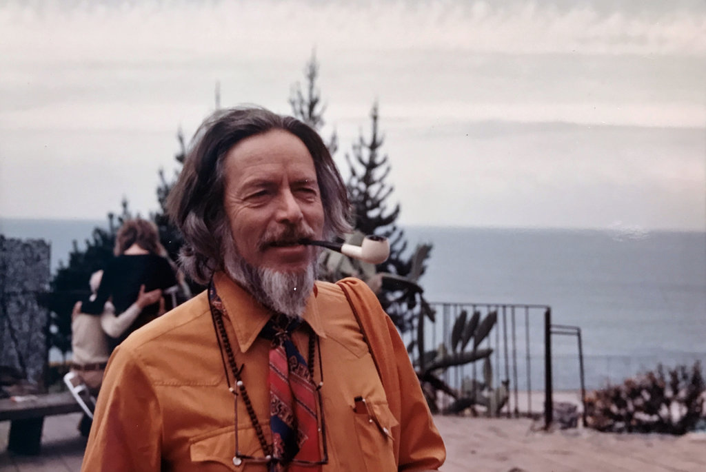 Alan Watts, orange shirt and pipe.