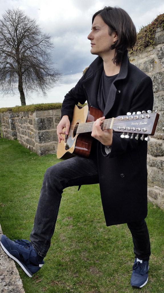 Sanjin playing 12 string guitar. Photo: Lisa Sinclair.